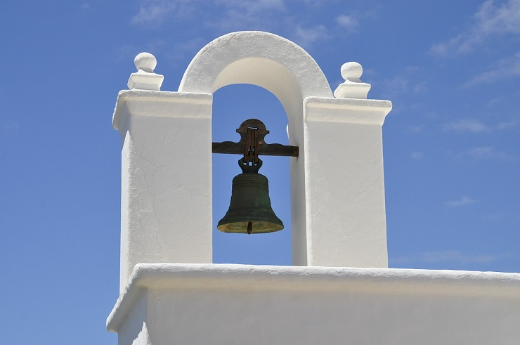 Cast iron bell against the blue skies – Spain