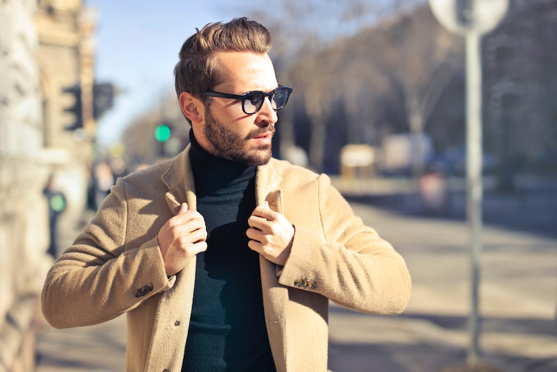 bearded man wearing glasses and coat in street