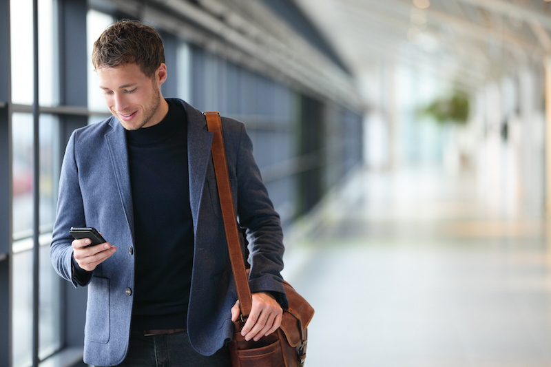 man on mobile phone in glass corridor smiling