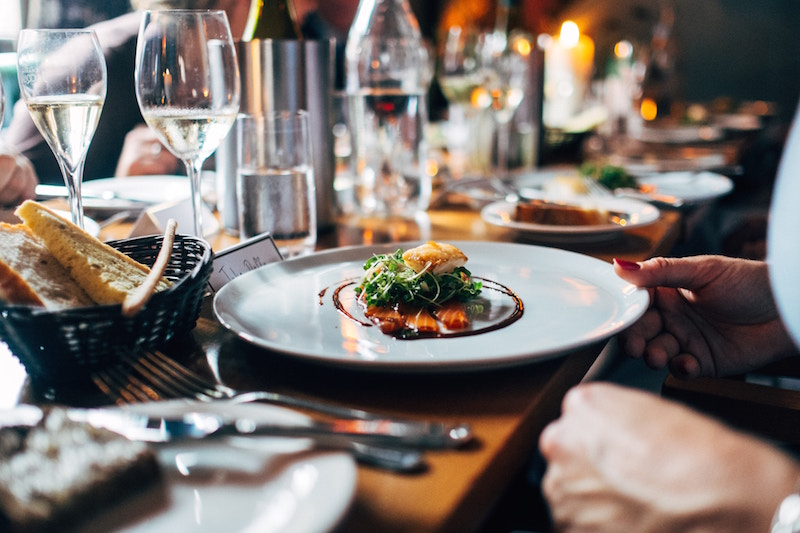 artistic dish of food on table in restaurant surrounded by glasses