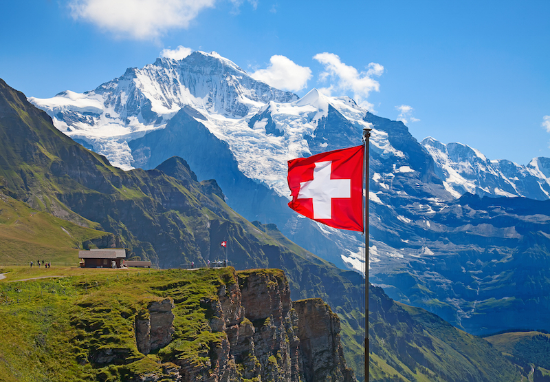 swiss flag flying in mountains
