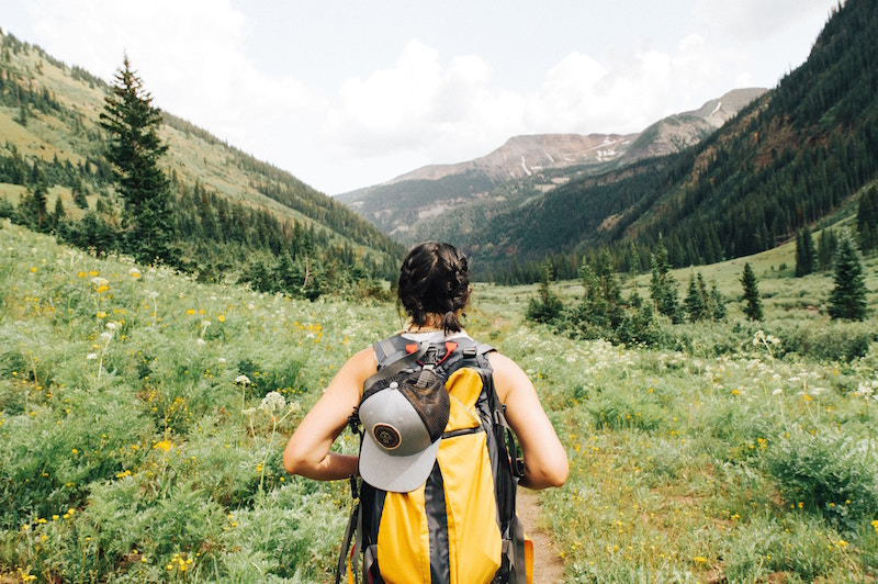women with backpack hking in hills