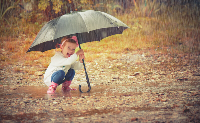 small girl smiling under umbrella in the rain