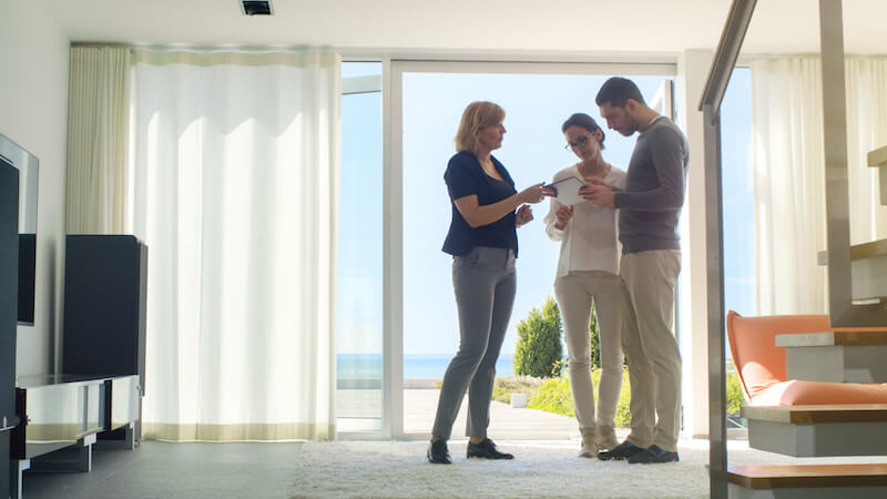 couple with realtor in sunny apartment living room
