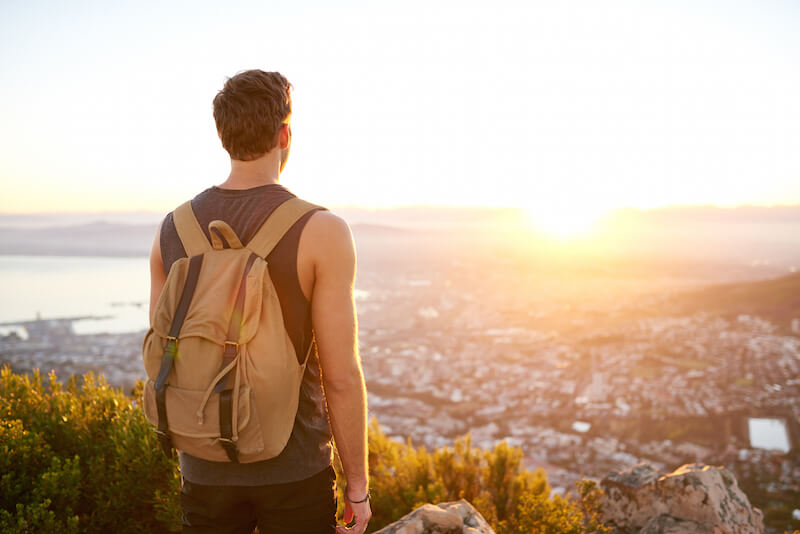 man standing on hill gazing at sunset