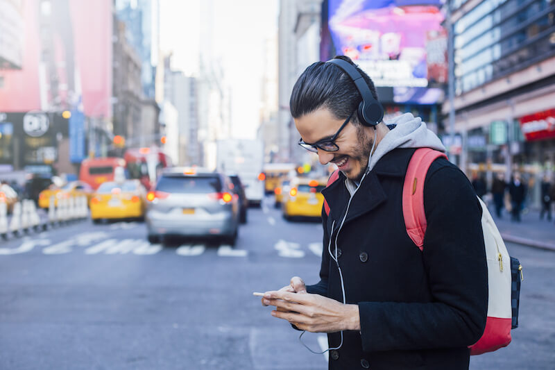 man wearing headphones smiling at mobile in new york city