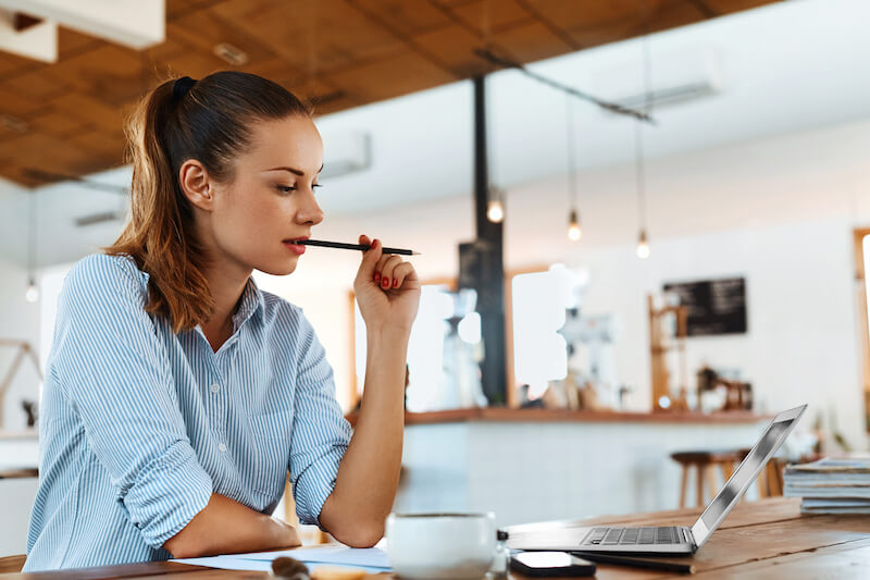 woman wearing glasses working at laptop with pencil