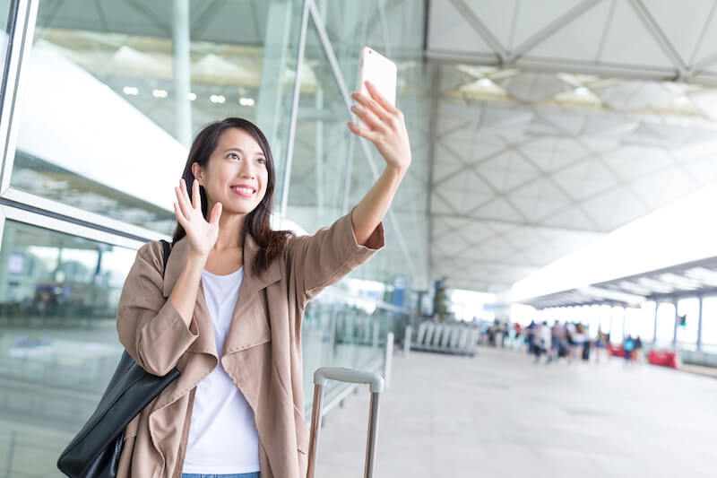 woman waving up on phone video call in airport
