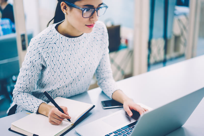 woman wearing glasses working at laptop biting a pencil