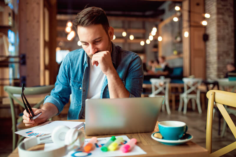worried man wearing glasses sitting at table with laptop and paper