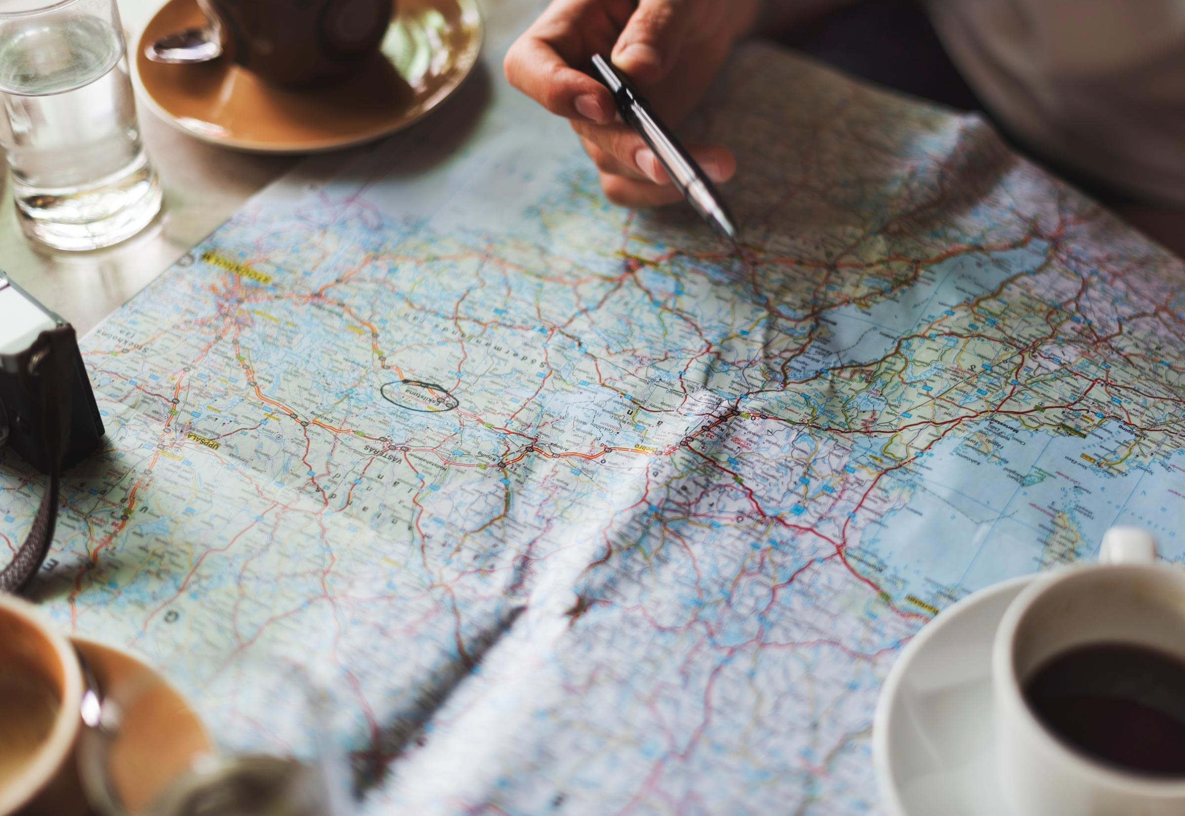 map on table with coffee cups
