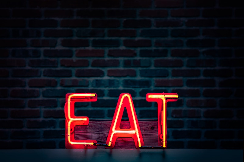 red led sign on wall of the word eat